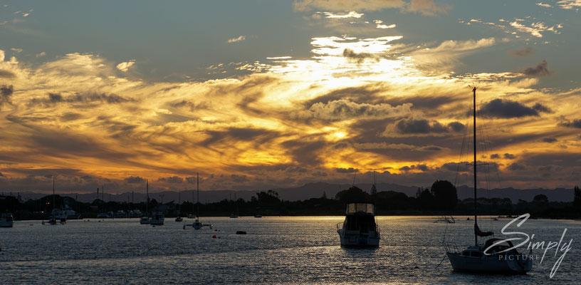 Whakatane, traumhafter Sonnenuntergang in der Hafenbucht mit gold-gelben Wolken