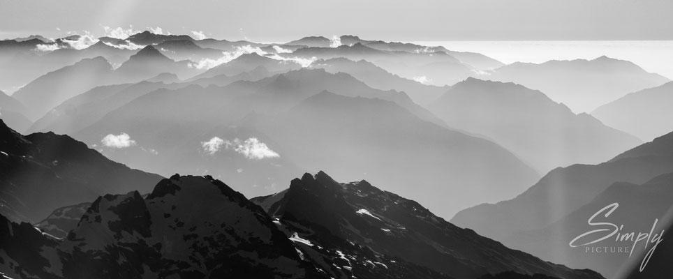 Flug über die südlichen Alpen,schwarzweiss Bild mit Bergen und Wolken, aus dem Flugzeug