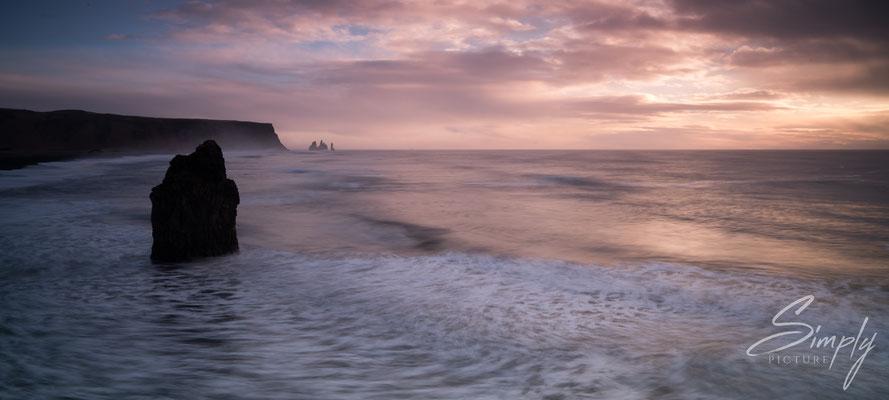 Leuchtende Abendstimmung mit grossen Gesteinsvormationen im rauschenden Meer am Kirkjufjara Beach.