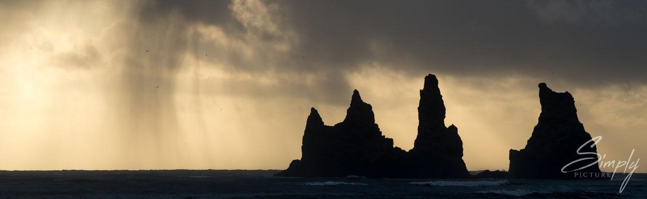 Spitzige Felsen im Meer mit goldiger Regenstimmung bei Reynisdrangar nähe Vík í Mýrdal.