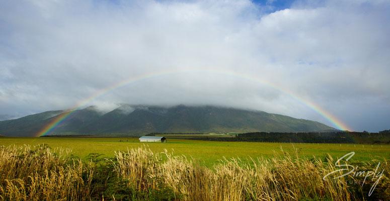 In der Nähe von Manapouri, Regenbogen über einem saftig grünen Feld mit einem kleinen Haus