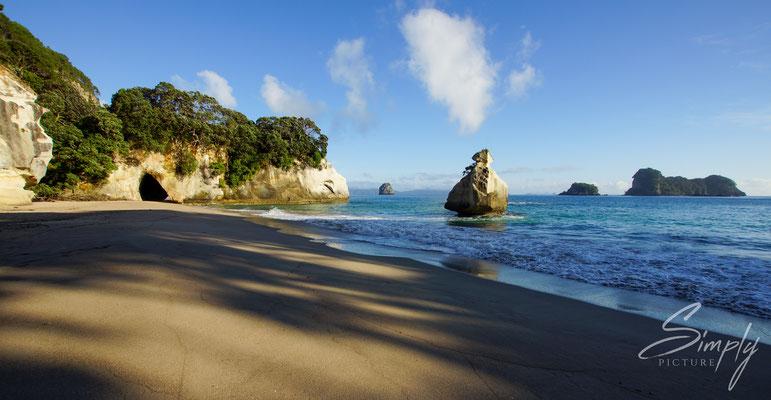 Hahei, Cathedral Cove, Menschenverlassener Strand kurz nach Sonnenaufgang-blauer Himmel mit einzelner Wolke