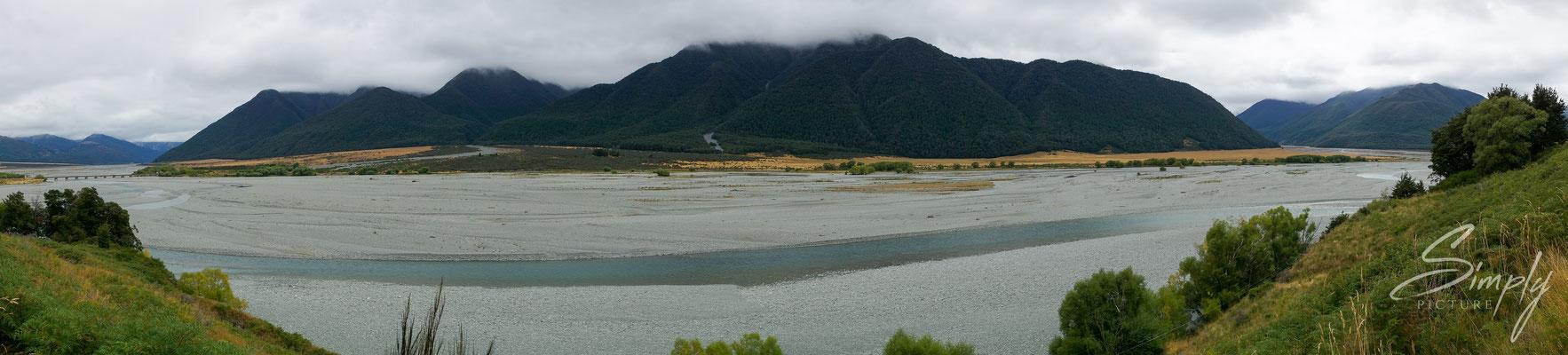 Canterbury, Flussbett mit viel Kies und intensiv, blauem Fluss in mitten der Berge und Wälder in den neuseeländischen Alpen