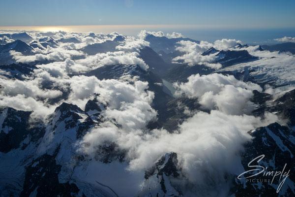 Flug über die südlichen Alpen, Wolkenmeer mit vielen Berggipfeln und dem Meer an dem Horizont