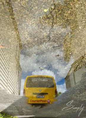 Russell, Reflektion eines Postauto's in einer Regenlache