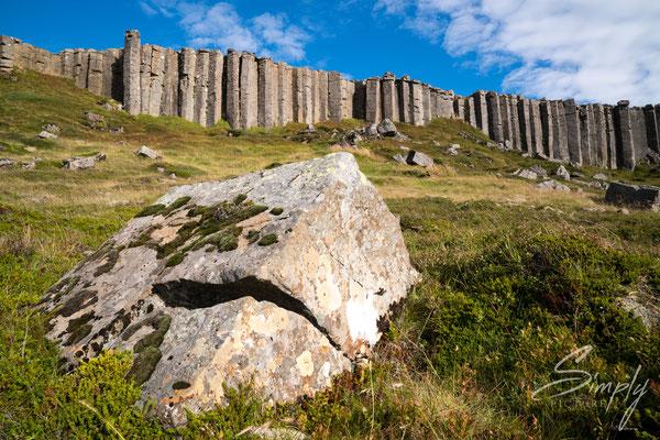 Gerðuberg Cliffs mit blauem Himmel und grünem Gras.