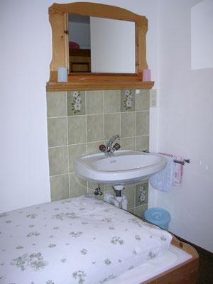 Waschbecken teilweise im Zimmer.