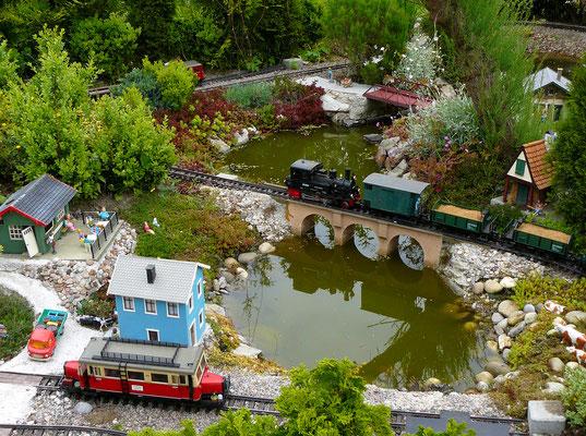 """Über die Brücke donnert ein Bauzug und stört so einige Gäste auf der Seeterrasse in """"Sachses Ruh"""". Der Triebwagen der Baureihe Wismar genannt """"Schweineschnäuzchen"""" wartet auf die ersten Ausflügler, die wieder heimwärts wollen."""