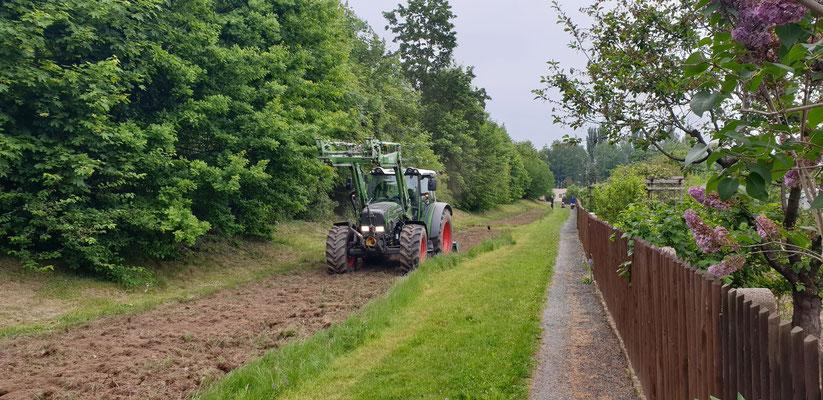 Traktor mit Motorhacke beim Zerkleinern und Glätten des Bodens
