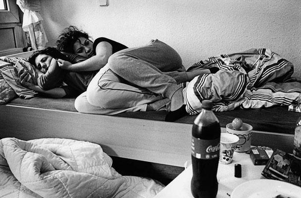 Zwei Frauen liegen zusammen in einem Einzelbett. Sie liegen auf der Seite und schauen beide gedankenverloren in den Raum. Eine Frau hat ihren Kopf auf der anderen abgelegt.