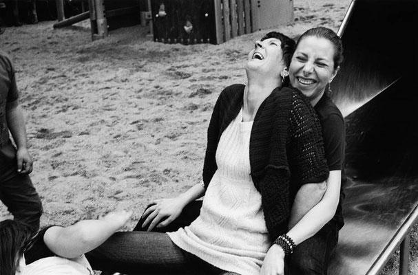 Zwei Frauen sitzen hintereinander auf dem Ende einer Rutsche. Die Vordere hat den Kopf nach hinten geworfen und lehnt mit ihrem Körper an der Hinteren. Beide lachen.