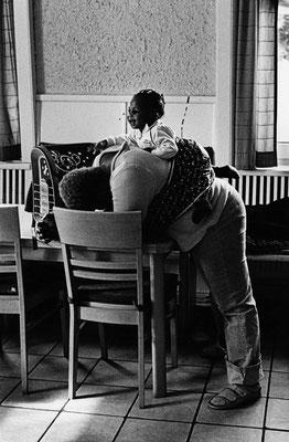 Eine Frau steht vor einem Tisch und lehnt mit dem Oberkörper auf dem Tisch. Ihr Kopf ist runtergebeugt und liegt auf ihren Armen. Mit einem Tuch trägt sie ein Kleinkind auf dem Rücken. Dieses lacht und schaut nach vorn in den Raum.