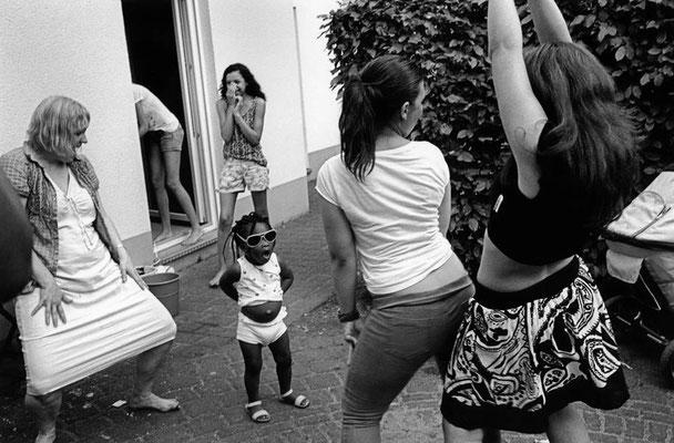 Drei Frauen und ein kleines Mädchen befinden sich im Innenhof des Hauses und tanzen. Eine weitere beobachtet das Ganze und wirkt amüsiert.