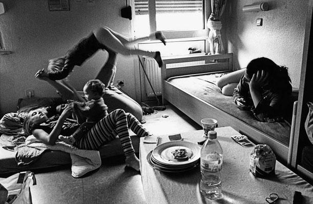 Eine Frau liegt im Einzelbett auf der Seite und schaut zwei weiteren Frauen zu, die mit ihren Kindern auf einer Matratze gegenüber auf dem Boden liegen. Sie spielen mit den Kindern.