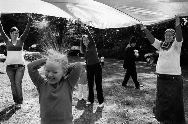 Frauen stehen im Garten im Kreis und halten ein Schwungtuch hoch. Sie lachen. Ein Mädchen steht in der Mitte unter dem Tuch. Sie lacht und hält die Hände hinter ihren Kopf. Einzelne Haarsträhnen sind durch den Schwung des Tuches hochgeflogen und stehen na