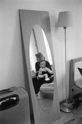 Zu sehen ist ein an der Wand gelehnter Spiegel. In diesem ist eine Frau zu sehen, welche auf der anderen Seite des Raumes auf dem Bett sitzt. Sie hat ein Kleinkind auf dem Schoß und hält dieses. Sie schaut in den Raum.