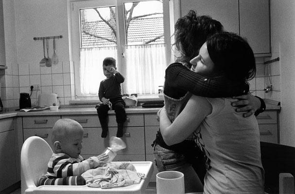 Alltagsgeschehen in der Küche. Ein Junge sitzt im Hintergrund auf der Küchenarbeitsfläche und reibt sich die Augen. Im Vordergrund sitzt eine Frau vor einem Kleinkind im Hochstuhl. Sie umarmt eine neben ihr stehende Frau.