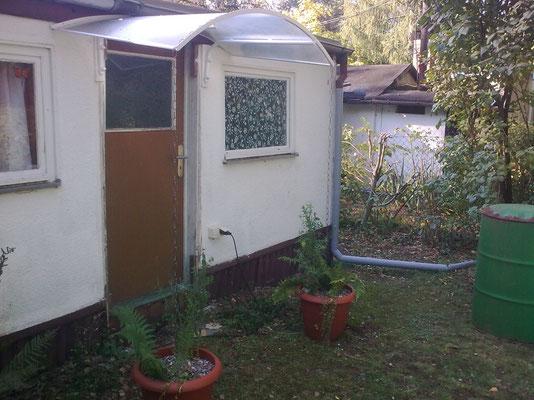 Eingang zum Abstellraum. Das Dach ist neu, der Regen wird mit Ketten in bepflanzte Kübel geleitet.
