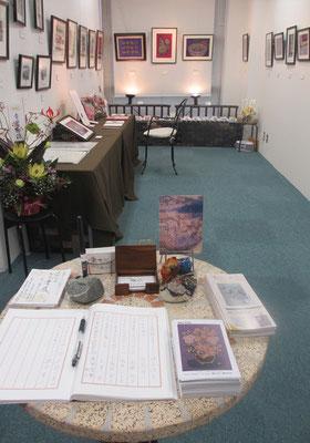 *丸いテーブルに芳名帳。作品展へようこそ*と板木彫り絵石クラフトのふくろう君。