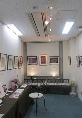 *入口からの展示風景。奥壁面に華やかな板木彫り絵作品。