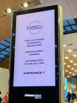 航空機では医療用マスクを配布し、付け替えを指示する表示(シャルル・ド・ゴール空港)