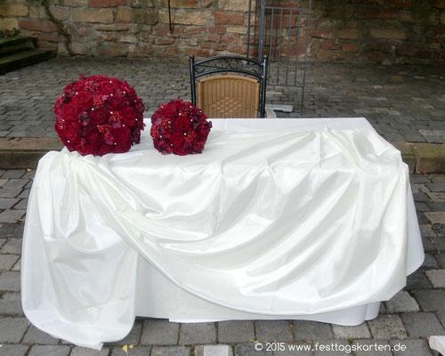 Trauplatzdekoration: Rote Rosen als Kugeln in zwei Größen auf drapiertem Seidentaft
