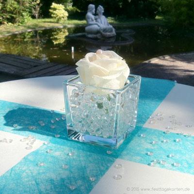 Stehtisch Dekoration für den Sektempfang nach der Trauung. Würfelglas gefüllt mit Aquaperls, solitärer Rosenkopf, Tischband und Raindrops.
