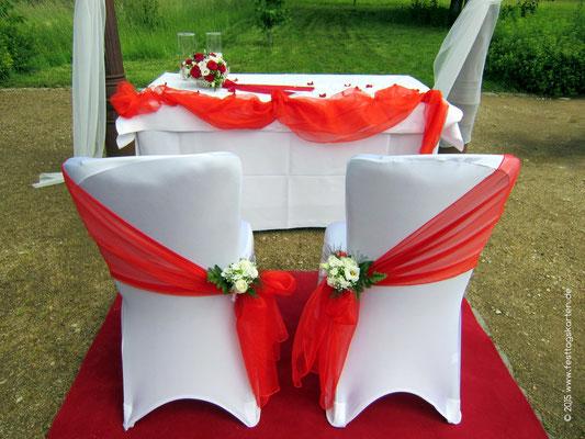 Geschmückte Brautpaar Stühle. Schärpe und Bouqet. Altar dekoriert mit Organza und Rosenherz.