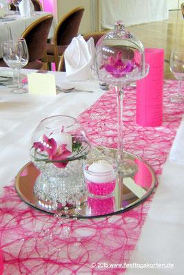 Tischdekoration in der Trendfarbe Pink: Tischband, runde Spiegelfliese, Teelichtglas mit Schwimmkerze, Kugelvase und Präsentoir mit Aquaperls, Orchideen und Gräsern dekoriert, Menü-Laternchen.