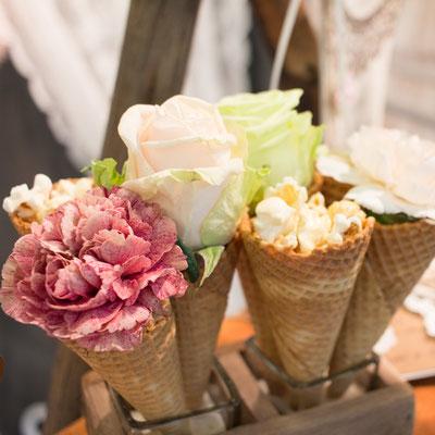 Blumen und Popcorn werden in Eiswaffeln arrangiert