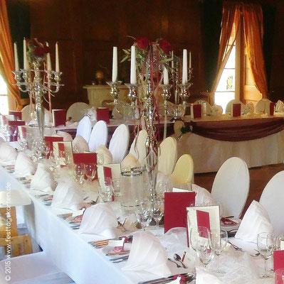 Opulente Tischdekoration mit hohen, ausdekorierten Kerzenleuchtern, Menükarten und Ehrenplatzdekoration
