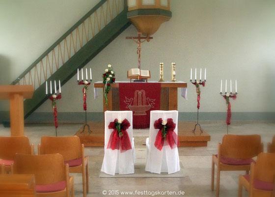 """Trauplatzdekoration, Stühle mit """"Fetter Schleife"""" mit Rose, Altargesteck und Kerzenleuchtern."""