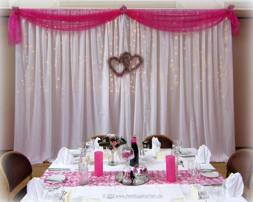 Ehrenplatzdekoration mit Doppelherzen aus roséfarbenem Schleierkraut gebunden.