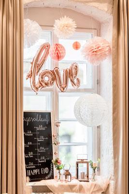 Dekoration in rosé mit Pompoms und Tafel mit Menükarte in Handlettering
