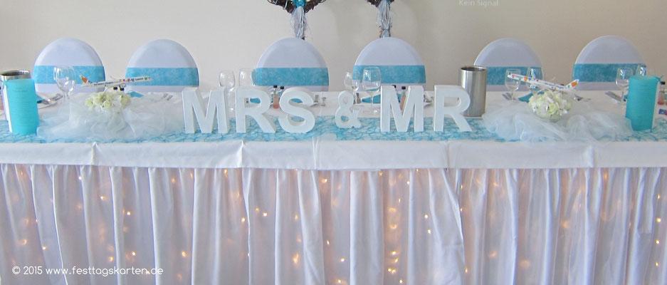 """Motto Hochzeit """"Flieger"""". Ehrenplatz mit Hinterleuchtung; Mrs & Mr; Organza """"Wolkenartig"""" drapiert, Rosengesteck mit """"Flieger""""."""