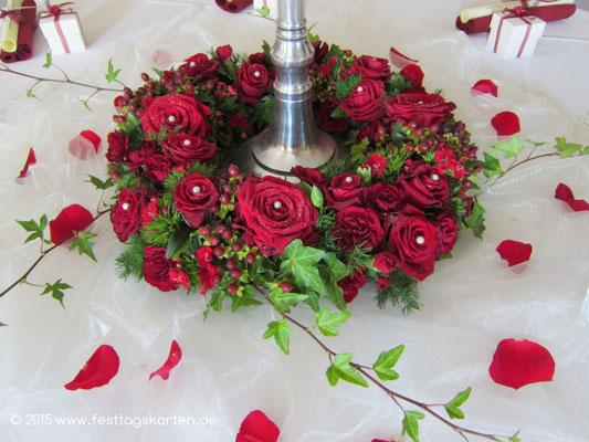 Rosenkranz Rote Rosen auf drapiertem Organza und gestreute Rosenblütenblätter
