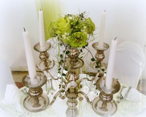 Kerzenleuchter ausdekoriert: Schlanke Weiße Kerzen, in der Mitte ein Arrangement aus Grünen Rosen und Wollfilz, Bändern und kleinen Engelsflügeln