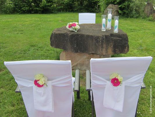 Trauplatz Dekoration: Bouqets an den Stühlen für das Brautpaar, Altargesteck und drei Zylindergläser mit den Kerzen für die Zeremonie