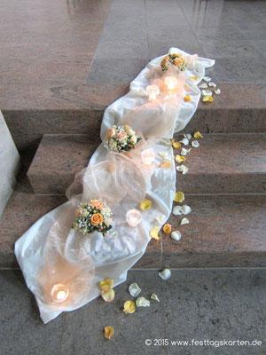Kirchenschmuck auf den Stufen zum Altar: Satin- und Organzastoff drapiert, kleine Bouqets, Windlichter und gestreute Rosenblütenblätter