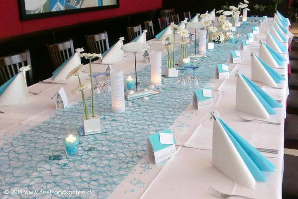 Festtafel anläßlich einer Konfirmation: Tischband, Fischdeko auf Spiegelfliese, Reagenzgläser mit Germini im Würfel, Gastgeschenke, Teelichtgläschen mit Raindrops befüllt.