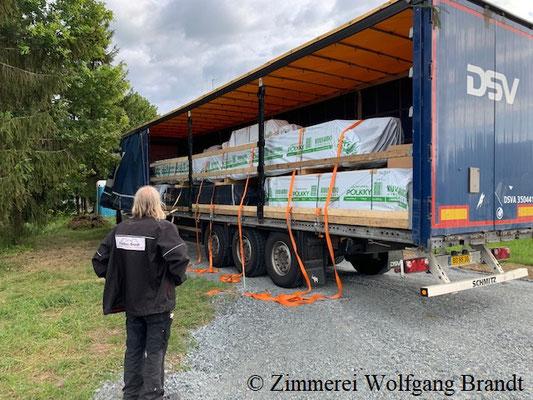 Blockhaus Holzbausatz ist überpünktlich auf der Baustelle - Das Entladen des ersten Trailers kann beginnen - Wolfsburg - Braunschweig - Bungalow - Lüneburg - Hannover - Niedersachsen - Stade - Melle - Neustadt - Göttingen - Goslar - Hildesheim - Holzhaus