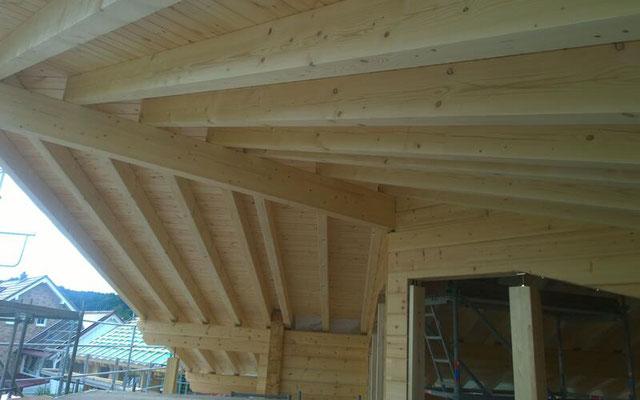 Bei der Dachkonstruktion dieses Hauses ist jeder Dachbalken ein Unikat - Blockhausbauer bei der Arbeit -