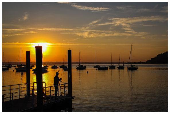Blick vom Steg des Yachthafens auf ankernde Schiffe und Angler bei Sonnenaufgang 9793