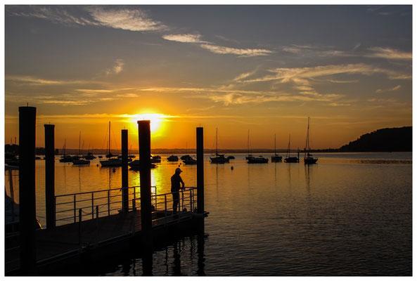 Blick vom Steg des Yachthafens auf ankernde Schiffe und Angler bei Sonnenaufgang 9799