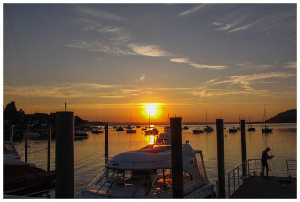 Blick vom Steg des Yachthafens auf ankernde Schiffe und Angler bei Sonnenaufgang 9782