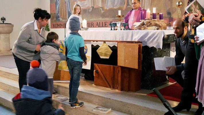 Dritter Adventsonntag, Kinder stellen das Bild der Heiligen Maria in die dritte Stall-Tür.