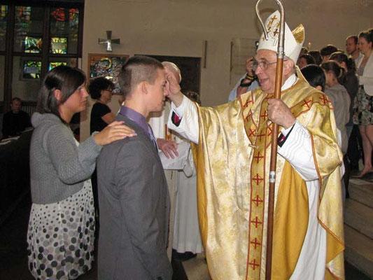 Weihbischof Krätzl spendet das Sakrament der Firmung. Die Paten legen die Hand auf die Schulter des Firmlings.
