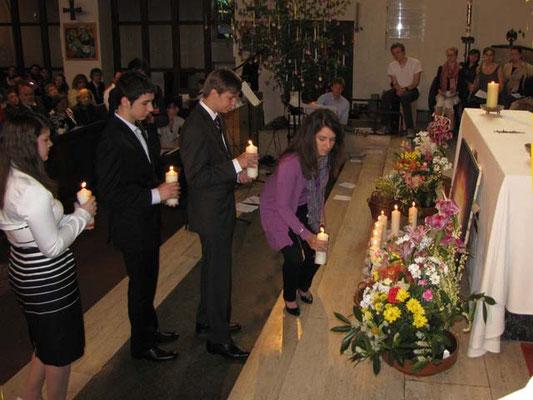 Die 11 Firmlinge stellen ihre Kerzen vor dem Altar auf. Die brennenden Kerzen bilden bis zum Ende der Messe ein stimmungsvolles Bild.