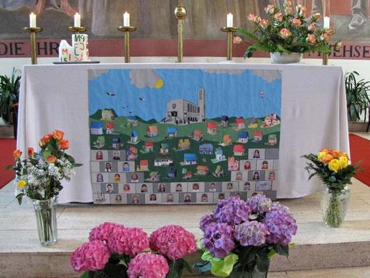 """Das Altartuch zeigt die Fotos der 31 Erstkommunion Kinder und zeigt auch passend zum Thema """"Gott baut ein Haus, das lebt"""" 31 Häuser."""