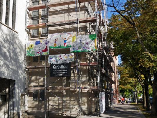 9.September: Jungschar hängt Banner am Gerüst auf und bringt Farbe ins Grau.